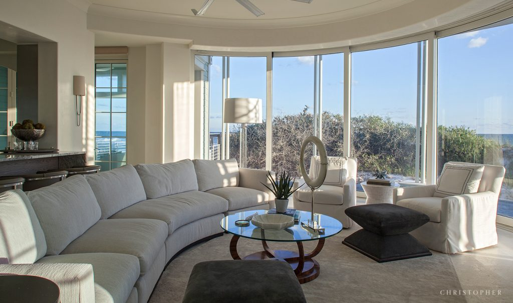 Coastal Luxury Living Room and Glass Motorized Wall System with Beach View